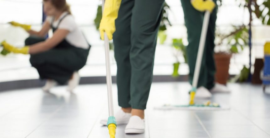 Close-up of person with yellow gloves cleaning the floor using a mop