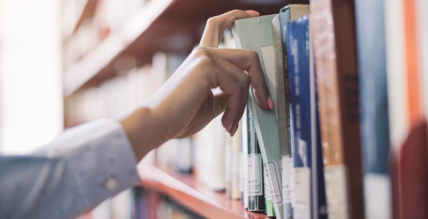 Woman at the library, she is searching books on the bookshelf and picking a textbook, hand close up