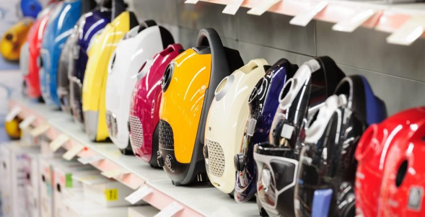 Row of variety vacuum cleaners in appliance store. Selective focus.
